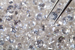Diamond held by tweezers close up. more diamonds out of focus in Royalty Free Stock Photography
