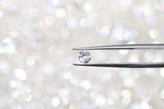 Diamond held by tweezers close up. more diamonds out of focus in Royalty Free Stock Photo