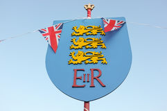 Diamond Jubilee Emblem & Bunting. A royal and British standard of coat of arms in celebration of the Queen's Diamond Jubilee of 2012 with British flags and royalty free stock image