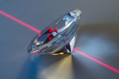 Diamond and laser. Closeup of a laser beam impacting on a cut crystal in a diamond Royalty Free Stock Photo