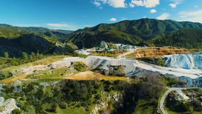 Diamond mine aerial view tracking pushing in flying slow hovering over mountains equipment blue sky. Showing reflections and work site stock video footage