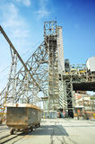 Diamond mine. Steel structure head gear of an active diamond mine with large capacity and hopper cart on rails in the forefront Royalty Free Stock Photography