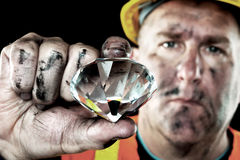 Diamond Miner. A dirty diamond miner covered in soot shows off a precious gem found in a coal mine Royalty Free Stock Photos