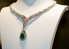 Diamond necklace. Necklace from white gold with diamonds and large emerald on Mannequin royalty free stock photo
