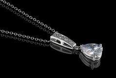 Diamond pendant with chain on black Royalty Free Stock Photos