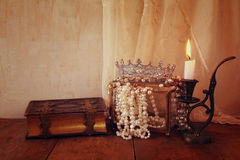Diamond queen crown, white pearls next to old book Royalty Free Stock Images