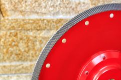 Fragment of a red diamond blade for cutting granite and stone against a background of a wall of golden sandstone royalty free stock photography