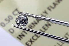 Diamond report. Cut diamond held by tweezers above certificate Royalty Free Stock Photos
