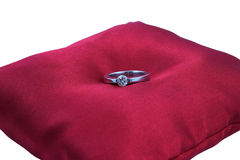 Diamond ring. Solitaire diamond ring on the red pillow, white background Stock Photos