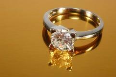 Diamond ring. Diamond platinum ring on gold background Stock Image