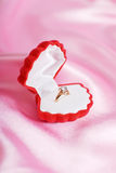 Diamond ring as a present. Red gift box and golden ring on pink silk Royalty Free Stock Photos