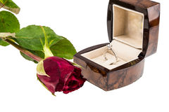 Diamond ring in box with red rose on white background Royalty Free Stock Image