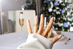 Diamond ring on a finger under the Christmas tree. Royalty Free Stock Images