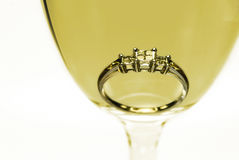 Diamond ring in a glass of white wine stock photography