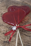 Diamond ring and heart shaped candies on wooden surface Royalty Free Stock Image