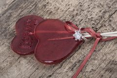Diamond ring and heart shaped red candies on wooden table Royalty Free Stock Images
