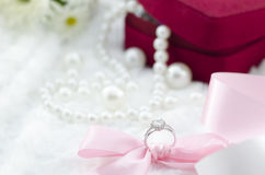 Diamond ring and pink ribbon on pearl necklace background Stock Image