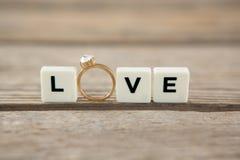 Diamond ring between white blocks displaying love message Stock Photos
