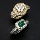 Diamond Rings. 2 diamond rings, one with emerald the other diamond studded Royalty Free Stock Photo