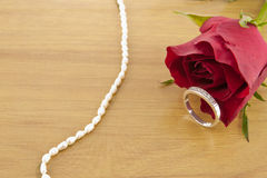 Diamond rings on wooden floor with rose decoration. Diamond rings on wooden floor with red rose decoration royalty free stock image