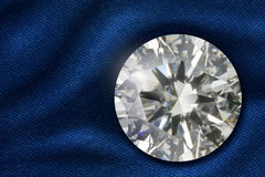 Diamond on satin fabric. A brilliant-cut round diamond on satin fabric Stock Images