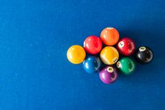 Diamond shape of 9-ball pool balls placed in rack position on blue felt table Royalty Free Stock Photo