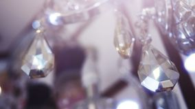 Diamond shape crystals on a beautiful chandelier. Close up on two beautiful shining crystals of a luxury chandelier. It is like two hanging diamonds on a stock video footage