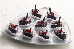 Diamond shaped chocolate confectionery. Diamond shaped gourmet chocolate confectionery or individual bonbons topped with maraschino cherries served on a stylish stock photo