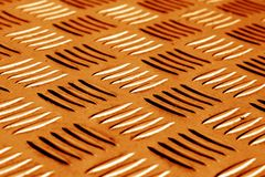 Diamond shaped metal floor pattern with blur effect in orange to Royalty Free Stock Photo