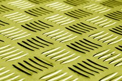 Diamond shaped metal floor pattern with blur effect in yellow to Royalty Free Stock Photography