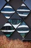 Diamond-shaped mirror panels on an exterior wall reflecting the adjacent buildings with brown vegetation in the foreground. Diamond-shaped mirror panels on an royalty free stock image