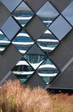 Diamond-shaped mirror panels on an exterior wall reflecting the adjacent buildings with brown vegetation in the foreground. Diamond-shaped mirror panels on an stock photo