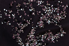 Diamond (small purple jewel) over black silk Royalty Free Stock Image