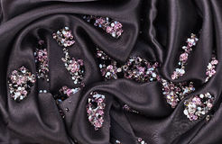 Diamond (small purple jewel) over black silk cloth Stock Photos