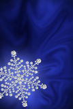 Diamond snowflake on a blue silk. Royalty Free Stock Photography