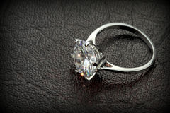 Diamond solitaire ring on black leather background Royalty Free Stock Images