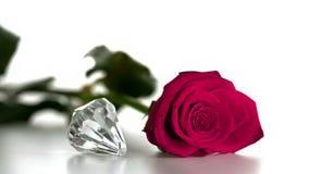 Diamond spinning beside pink rose stock video footage