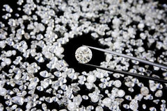 Diamond In Tweezers. A large diamond held in tweezers with other diamonds in the background royalty free stock photography
