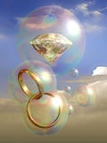 Diamond wedding. A diamond and two wedding rings into soap bubbles Royalty Free Stock Photography