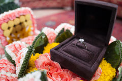 A diamond wedding ring in an open box on traditional Thai style. Garland Royalty Free Stock Photography