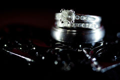 Diamond Wedding Rings in Black Textured Background Stock Image