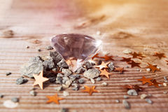 Diamond on a wooden table. A diamond with stones and stars on a wooden table Stock Photography