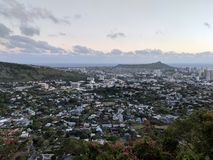 Diamondhead and the city of Honolulu, Kaimuki, Kahala, and ocean. Scape on Oahu on a nice day at dusk viewed from high in the mountains with tall trees in the royalty free stock photography