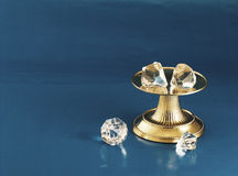 Diamonds. Gold pedestal with diamonds on it and two beside it.  Blue background Stock Photo