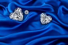 Diamonds on blue luxurious cloth silk, wavy fabric satin and gemstone.  stock photography