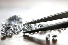 Diamonds. Brilliant cut diamond held by tweezers royalty free stock images