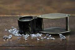 Diamonds. Brilliant cut diamonds with folding magnifier on wooden background royalty free stock photo
