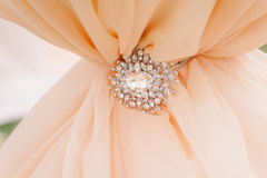 Diamonds brooch on peachy satin as a background. Diamonds and silver brooch on peachy satin as a background Royalty Free Stock Photos