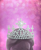Diamonds crown on women head in pink glitter backg Stock Photo