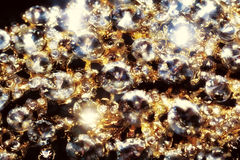 Diamonds and Gold Macro. Diamonds in different sizes, golden jewelry close up background Stock Photo